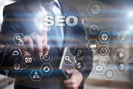 selecting: Businessman is pressing on the virtual screen and selecting SEO. Stock Photo