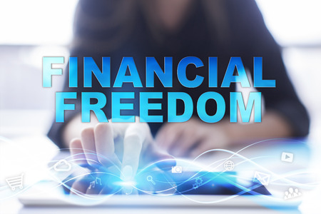 debt goals: Woman is using modern tablet pc, presssing on touch screen and selecting Financial freedom.