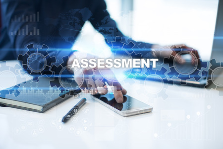 assessments: Businessman is working in office, pressing button on virtual screen and selecting assessment. Stock Photo