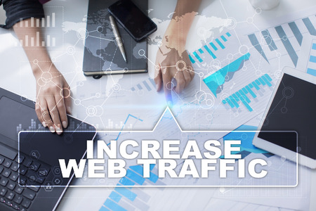 web traffic: Woman is working with documents, tablet pc and notebook and selecting increase web traffic.