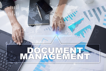 Woman is working with documents, tablet pc and notebook and selecting document management.