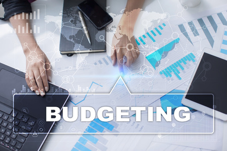 budgeting: Woman is working with documents, tablet pc and notebook and selecting budgeting. Stock Photo