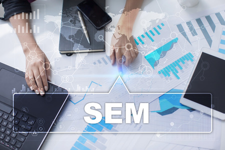 adwords: Woman is working with documents, tablet pc and notebook and selecting sem. Stock Photo