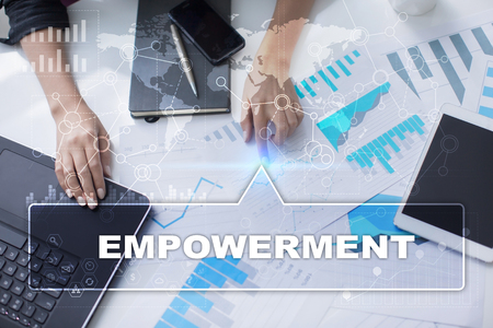 enabling: Woman is working with documents, tablet pc and notebook and selecting empowerment. Stock Photo
