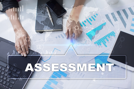 assessments: Woman is working with documents, tablet pc and notebook and selecting assessment. Stock Photo