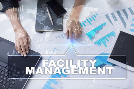 Woman is working with documents, tablet pc and notebook and selecting facility management.