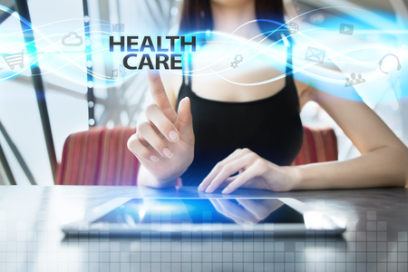 Woman is using tablet pc, pressing on virtual screen and selecting health care Stock Photo