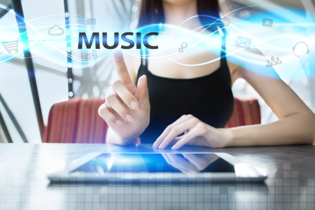 shool: Woman is using tablet pc, pressing on virtual screen and selecting music Stock Photo