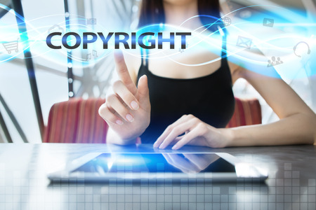 patents: Woman is using tablet pc, pressing on virtual screen and selecting copyright Stock Photo