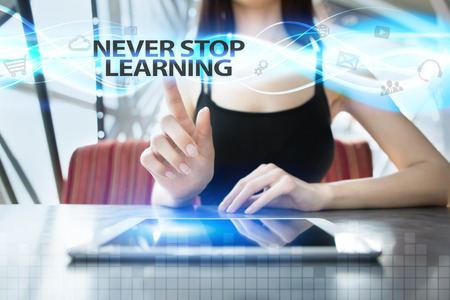 Woman is using tablet pc, pressing on virtual screen and selecting never stop learning Stock Photo