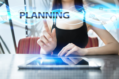 selecting: Woman is using tablet pc, pressing on virtual screen and selecting planning Stock Photo