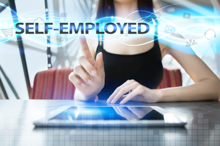 selfemployed: Woman is using tablet pc, pressing on virtual screen and selecting self-employed Stock Photo