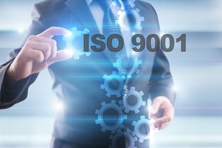 Geschäftsmann, der ISO 9001 auf virtuellem Schirm vorwählt. Standard-Bild - 65795129
