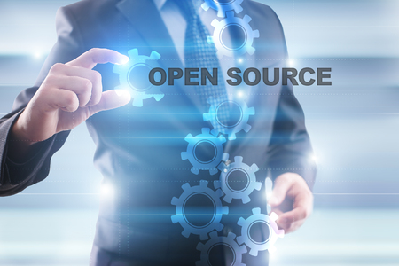 open source: Businessman selecting open source on virtual screen.