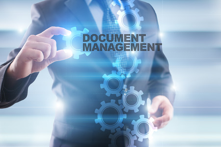 document management: Businessman selecting document management on virtual screen. Stock Photo