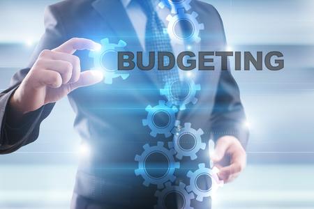 budgeting: Businessman selecting budgeting on virtual screen. Stock Photo