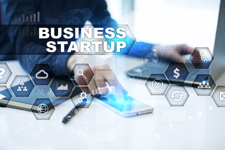 selecting: Businessman is working in office, pressing button on virtual screen and selecting business startup