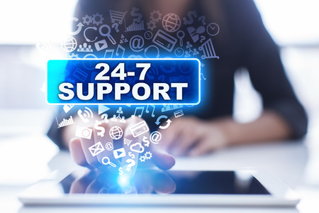 24x7: Woman is using tablet pc, pressing on virtual screen and selecting 24-7 support. Stock Photo