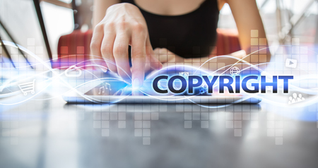 patents: Woman using tablet pc and selecting copyright. Stock Photo