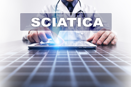 spinal disks: Medical doctor working with modern computer and selecting sciatica. Medical concept. Stock Photo