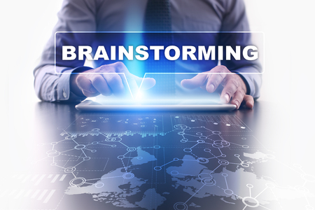 selecting: Businessman is using tablet pc, pressing on virtual screen and selecting brainstorming.