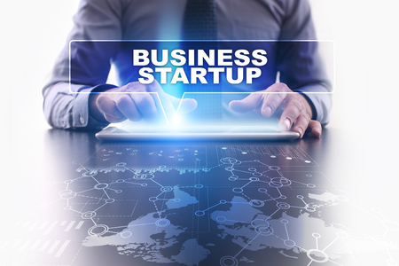 selecting: Businessman is using tablet pc, pressing on virtual screen and selecting business startup.