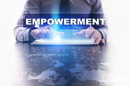 enabling: Businessman is using tablet pc, pressing on virtual screen and selecting empowerment.