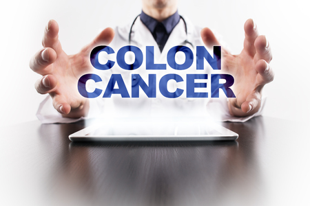 rectal: Medical doctor using tablet PC with colon cancer medical concept.