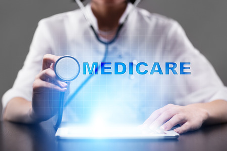 Medical doctor working with modern computer and pressing button medicare. Medical concept.