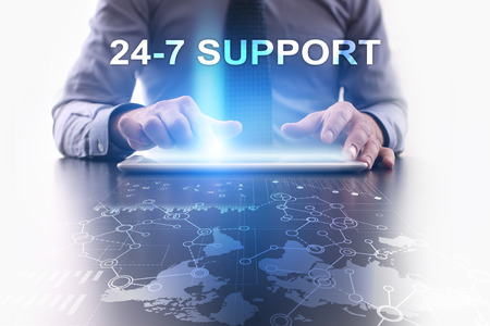 24x7: Businessman is using tablet pc and selecting 24-7 support. Stock Photo