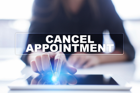 appointing: Woman is using tablet pc, pressing on virtual screen and selecting cancel appointment. Stock Photo