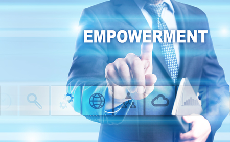 enabling: Businessman pressing button on touch screen interface and selecting Empowerment. Stock Photo