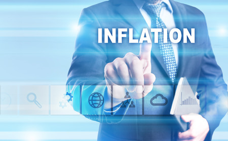 Businessman pressing button on touch screen interface and selecting Inflation. Stock Photo