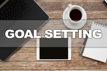 Tablet on desktop with goal setting text.