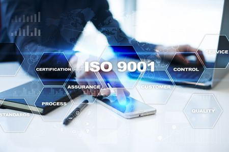 Businessman is working in office, pressing button on virtual screen and selecting iso 9001.