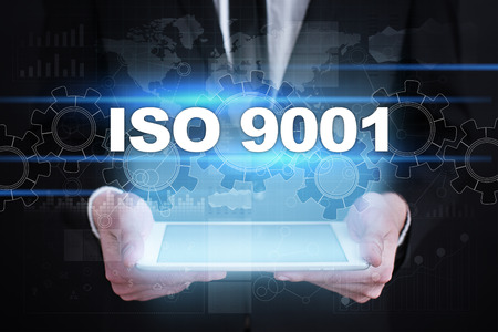 Businessman holding tablet PC with iso 9001  concept.