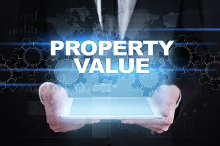 Businessman holding tablet PC with property value concept. Stock fotó
