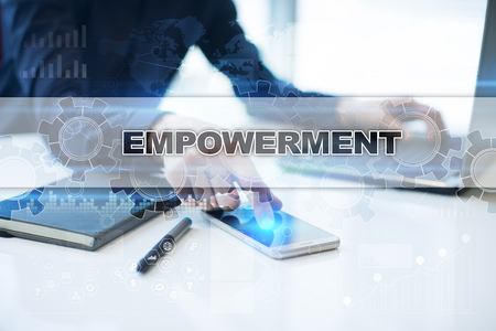 enabling: Businessman working in office, pressing button on virtual screen and selecting empowerment. Stock Photo