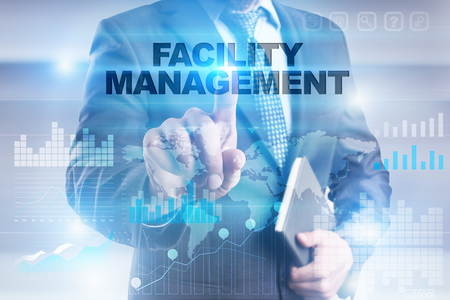 Businessman pressing button on touch screen interface and selecting facility management. 写真素材