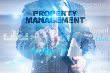 Businessman pressing button on touch screen interface and selecting property management. Stock Photo