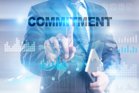 Businessman pressing button on touch screen interface and selecting commitment.