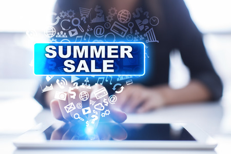 Woman is using tablet pc, pressing on virtual screen and selecting summer sale. Stock Photo