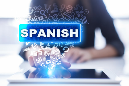 Woman is using tablet pc, pressing on virtual screen and selecting spanish.