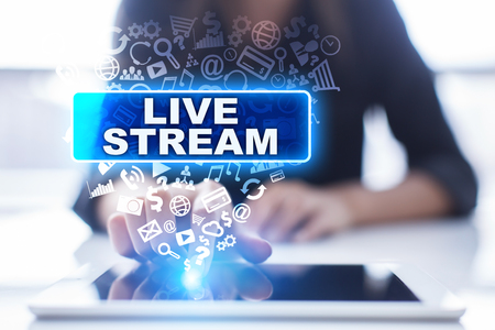Woman is using tablet pc, pressing on virtual screen and selecting live stream.