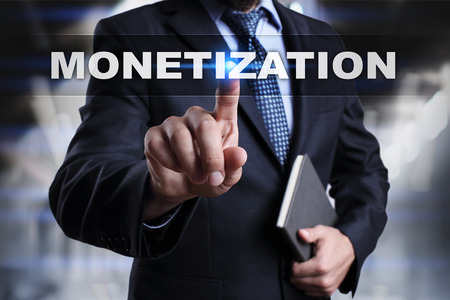 Businessman is pressing button on touch screen interface and selecting monetization.