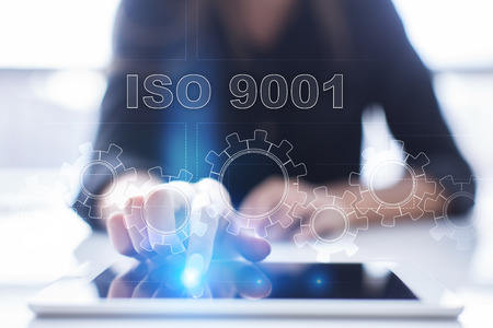 Woman is using tablet pc, pressing on virtual screen and selecting iso 9001 . Stock Photo