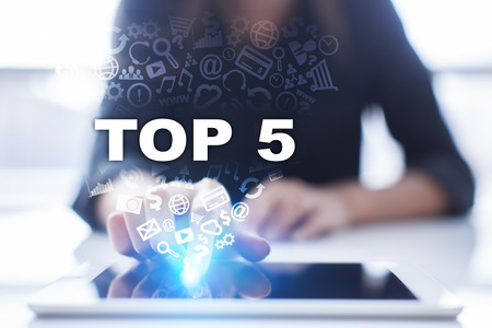 Woman is using tablet pc, pressing on virtual screen and selecting top 5. Stock Photo