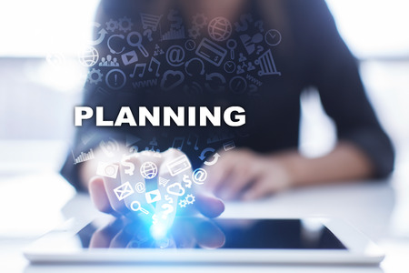 Woman is using tablet pc, pressing on virtual screen and selecting planning.