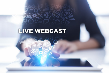 Woman is using tablet pc, pressing on virtual screen and selecting live webcast. Stock Photo