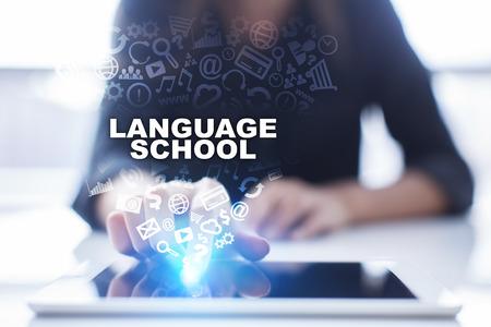 La mujer está usando la PC de la tableta, presionando en la pantalla virtual y seleccionando la escuela de idiomas. Foto de archivo - 73624330